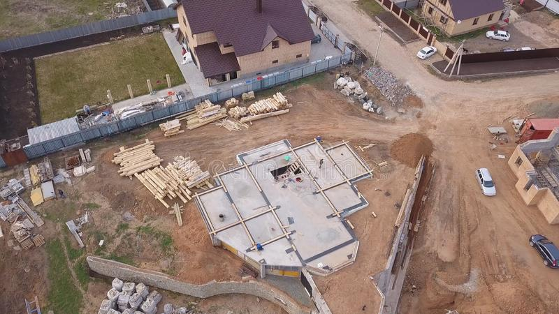 Aerial view of new modern cottage near the building site, construction materials and workers pouring concrete for the. Foundation. Process of new building stock images