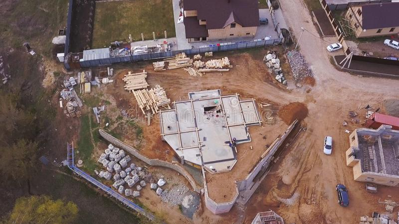 Aerial view of new modern cottage near the building site, construction materials and workers pouring concrete for the. Foundation. Process of new building stock image