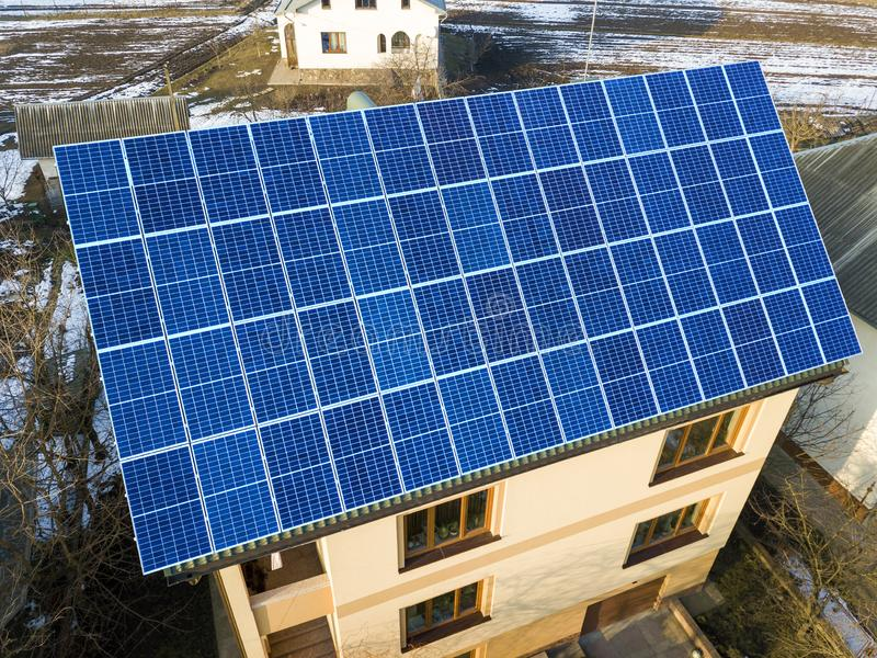 Aerial view of new modern two story house cottage with blue shiny solar photo voltaic panels system on the roof. Renewable. Ecological green energy production royalty free stock image