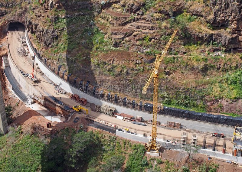 Aerial view of a new road under construction with crane and construction materials and machinery working on the site with a tunnel. Being excavated through the royalty free stock photos