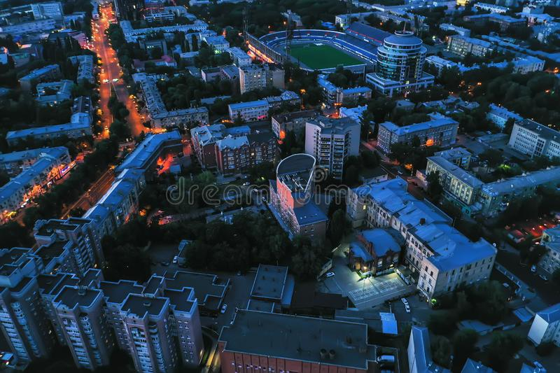 Aerial view of night city with illuminated roads, car traffic and different buildings, drone shot stock image