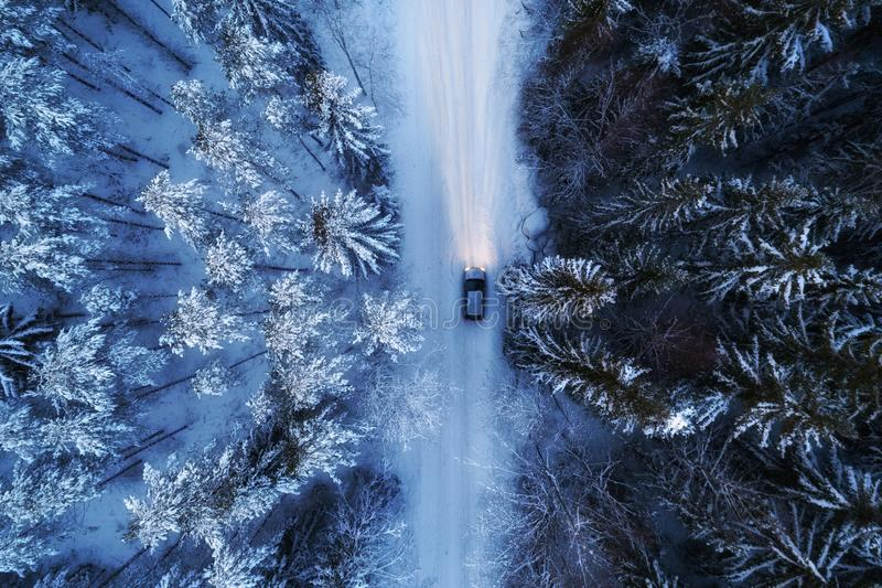 Aerial view of night forest covered by snow, road and car passing by. stock image