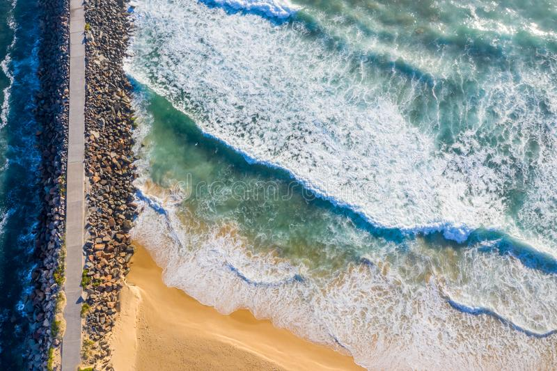 Aerial view of Nobbys Breakwall. A straight down view of the Breakwall at Nobbys Beach - Newcastle Australia with rough surf pounding onto the shoreline. Nobbys stock image