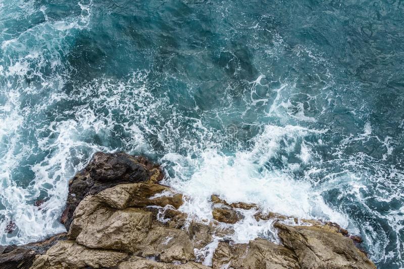 Aerial view of ocean wave crashing on rocky cliff with white spray and foam on deep blue sea water after storm stock photo