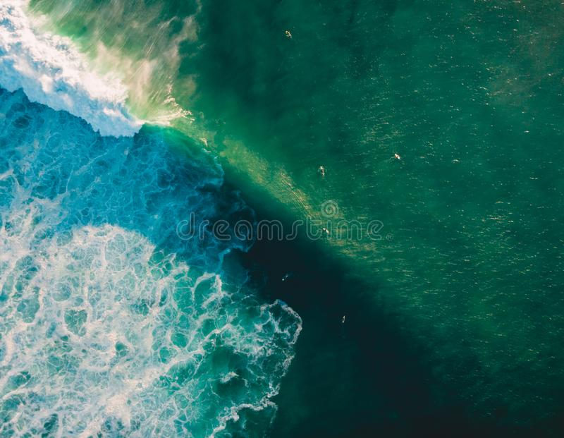 Aerial view of ocean with wave and surfers. Big barrel wave royalty free stock image