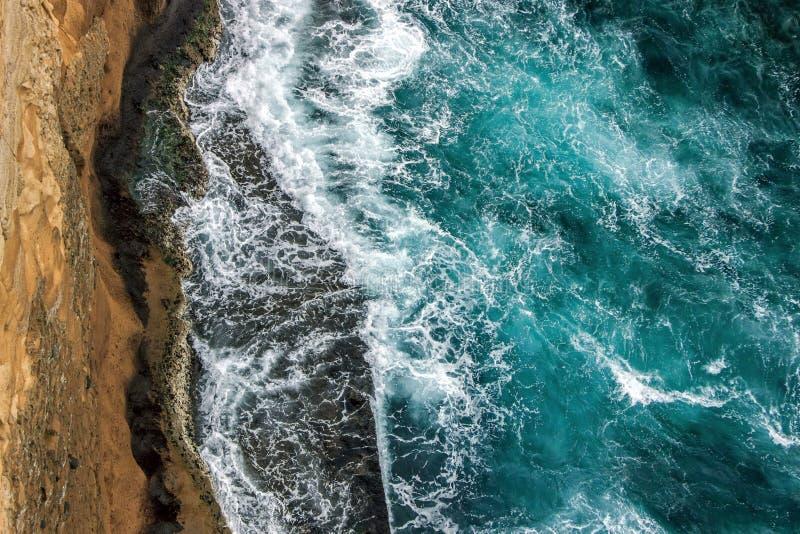 Aerial view of ocean waves on cliff. Aerial view of ocean waves wash up on cliff stock photo