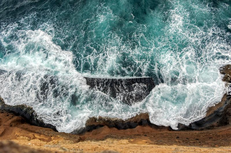 Aerial view of ocean waves on cliff. Aerial view of ocean waves wash up on cliff royalty free stock images