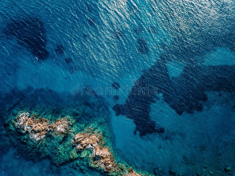 Aerial view of ocean waves and rocks. Blue sea surface. Aerial view of ocean waves and rocks. Blue and turquoise sea surface stock image