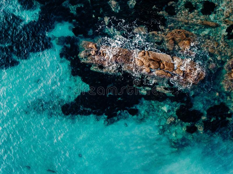 Aerial view of ocean waves and rocks. Blue sea surface. Aerial view of ocean waves and rocks. Blue and turquoise sea surface stock photography