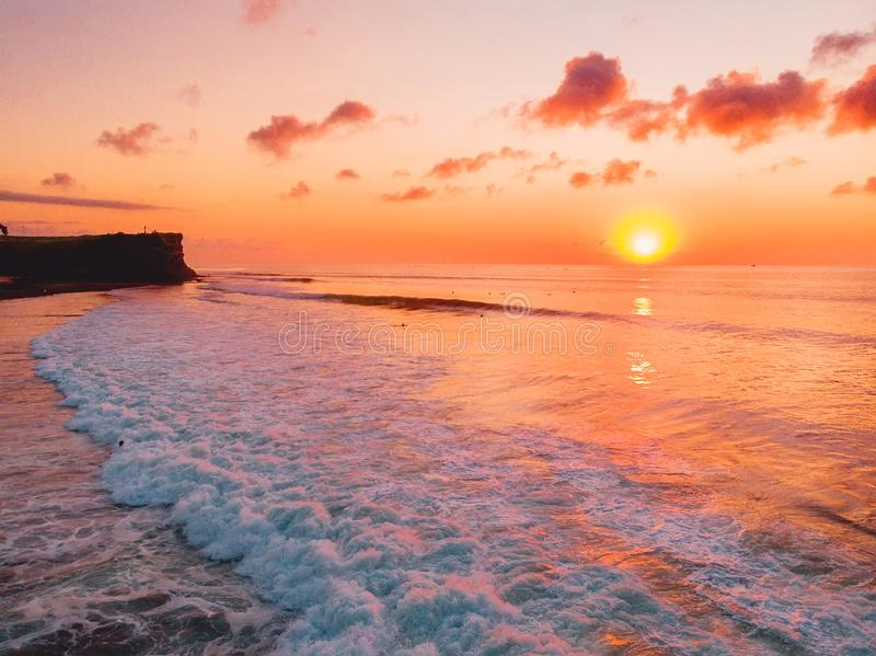 Aerial view of ocean with waves, surfers and sunset in Bali. Aerial view of ocean with waves, surfers and sunset royalty free stock photography