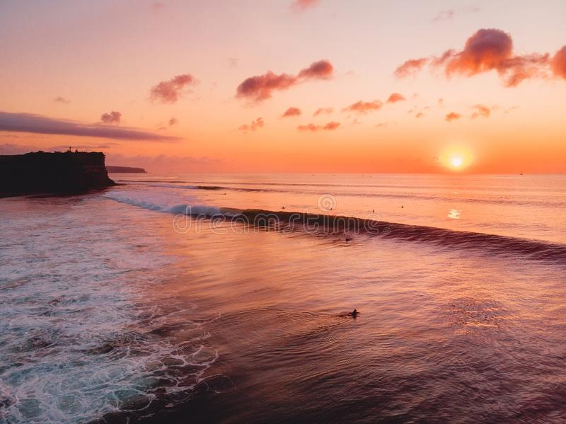 Aerial view of ocean with waves, surfers and warm sunset in Bali. Aerial view of ocean with waves, surfers and warm sunset royalty free stock images