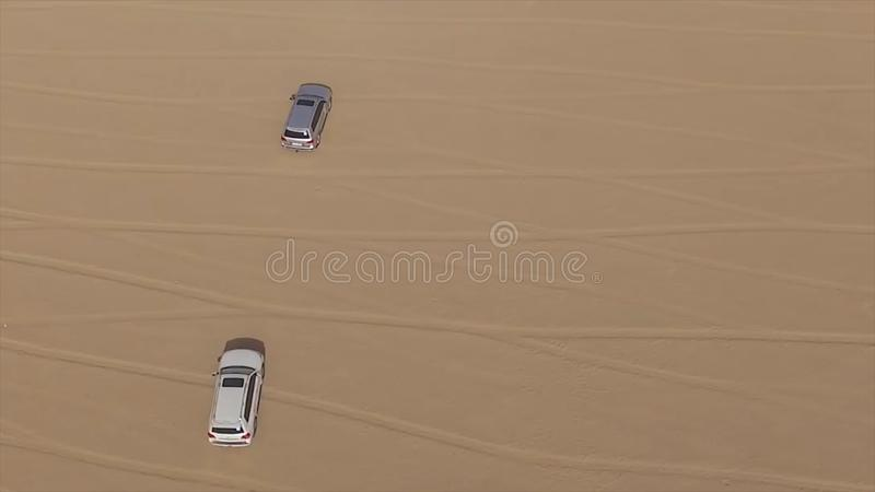 Aerial view of 4x4 off road land vehicle taking tourists on desert dune bashing safari in Dubai, UAE. AERIAL: cars in a. Dry riverbed royalty free stock photo