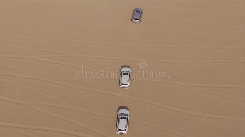 Aerial view of 4x4 off road land vehicle taking tourists on desert dune bashing safari in Dubai, UAE. AERIAL: cars in a. Dry riverbed stock images