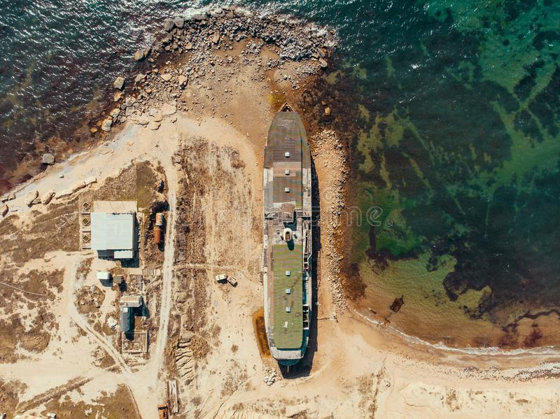 Aerial view of old abandoned rusted ship aground after shipwreck accident in Crimean coast on sand beach. Drone shot stock photos