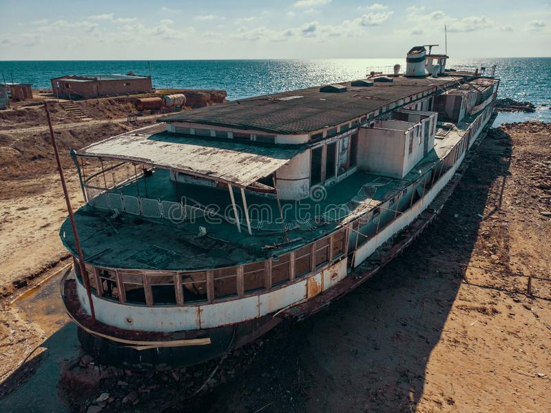 Aerial view of old abandoned rusted ship aground after shipwreck accident in Crimean coast on sand beach. Drone shot royalty free stock photo