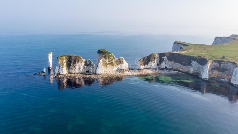 An aerial view of the Old Harry Rocks along the Jurassic coast with crystal clear water and white cliffs under a hazy sky stock photos