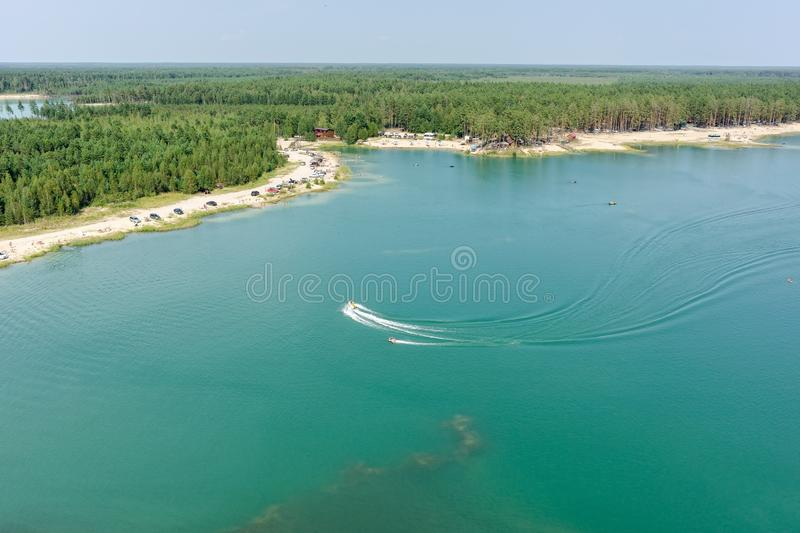 Aerial view of Blue Lake beach in Tyumen. Russia. Aerial view onto beach on so-calles Blue Lake and hydrocycle tows the inflatable watercraft circle. Tyumen stock image