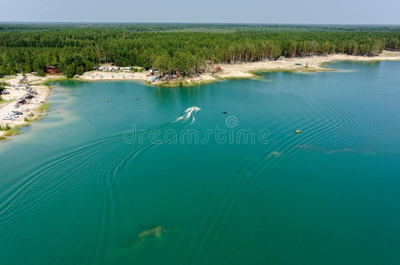 Aerial view of Blue Lake beach in Tyumen. Russia. Aerial view onto beach on so-calles Blue Lake and hydrocycle tows the inflatable watercraft circle. Tyumen royalty free stock images