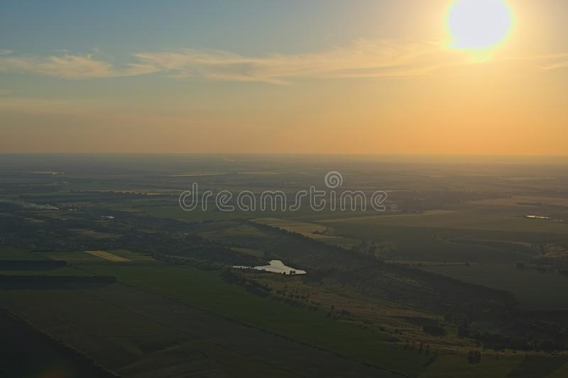 Aerial view over the agricultural fields and little lake during sunset. Kyiv region, Ukraine royalty free stock photos