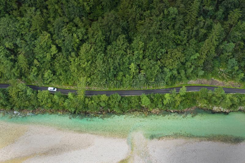 Aerial view over  green tree forest and river with a road going through with a transport van royalty free stock photo