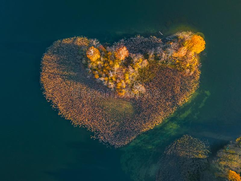 Aerial view over an island. The island is formed as a green heart. Surrounded by water, ocean, sea, lake stock images
