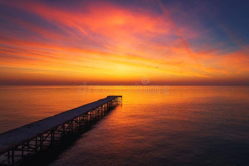 Aerial view over the old broken bridge in the sea, sunrise shot. stock photos