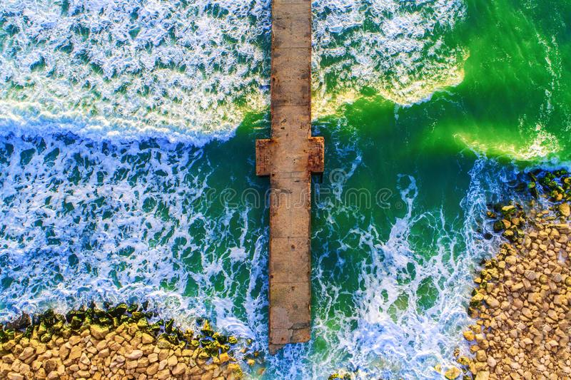 Aerial view over the old broken bridge in the sea, sunrise shot. royalty free stock photos