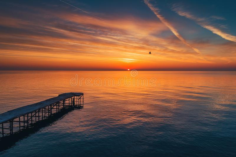 Aerial view over the old broken bridge in the sea, sunrise shot. stock photography