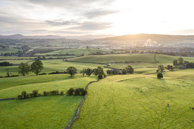 Aerial View over Scenic Countryside Fields in UK. Rolling countryside hills at hazy sunrise near Kendal in Lake District National Park, United Kingdom stock image
