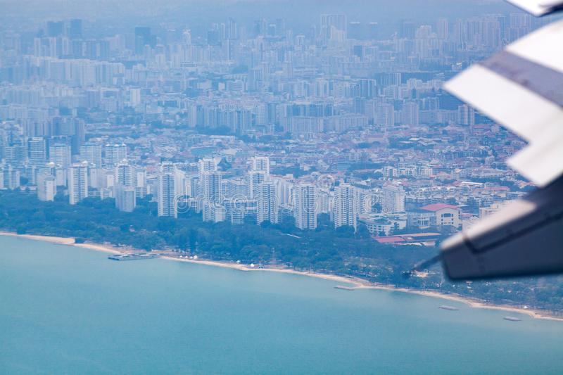 aerial view over Singapore and airplane wings royalty free stock image