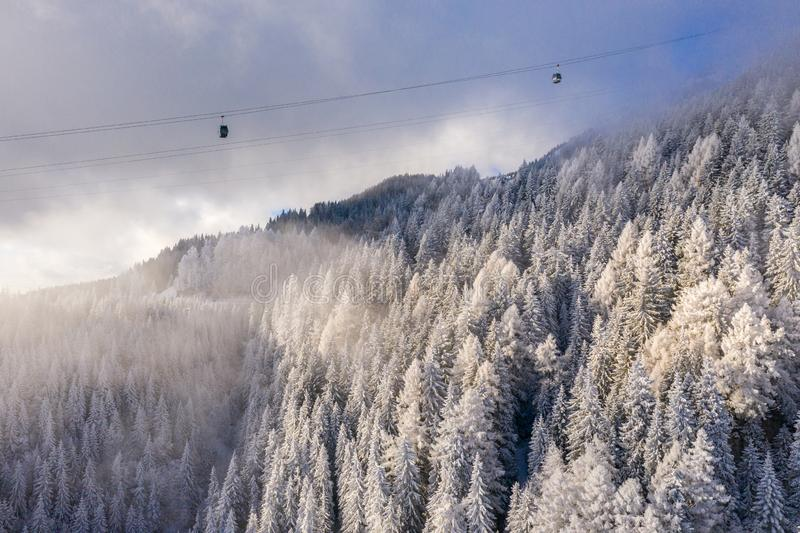 Aerial view over snowy mountain ridge valley with clouds, cable car lifting. Mountain winter forest. Tourist gondola transportatio stock photography