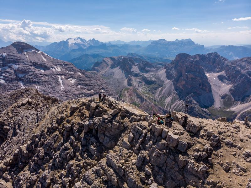 Aerial view over  Tofana Di Mezzo peak in Dolomites. Climbers on top of the mountains. People silhouette on the summit. On the rid stock photos