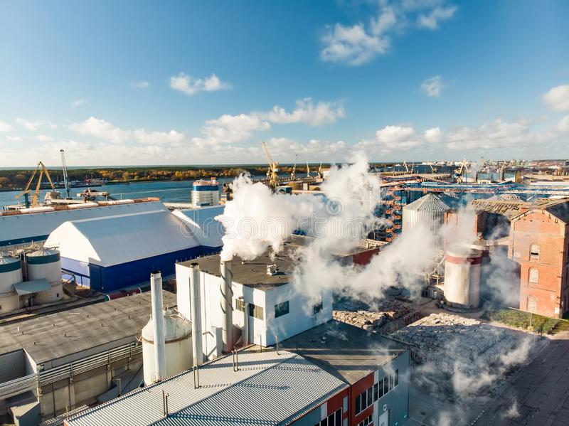 Aerial view of paper and wood industry company building complex during operational process resulting in intensive white fume. Aerial view of paper and wood stock image