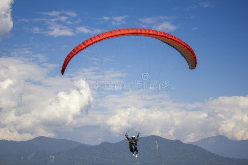 Aerial view of paraglider with a red parachute in a blue sky with white clouds over green mountainsaerial view of paraglider with royalty free stock photos
