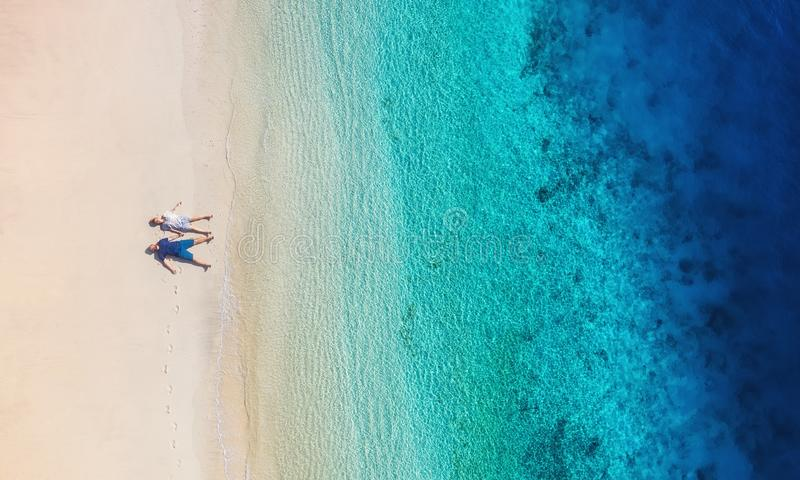 Aerial view of a people couple on the beach on Bali, Indonesia. Vacation and adventure. Beach and turquoise water. Top view from d stock image