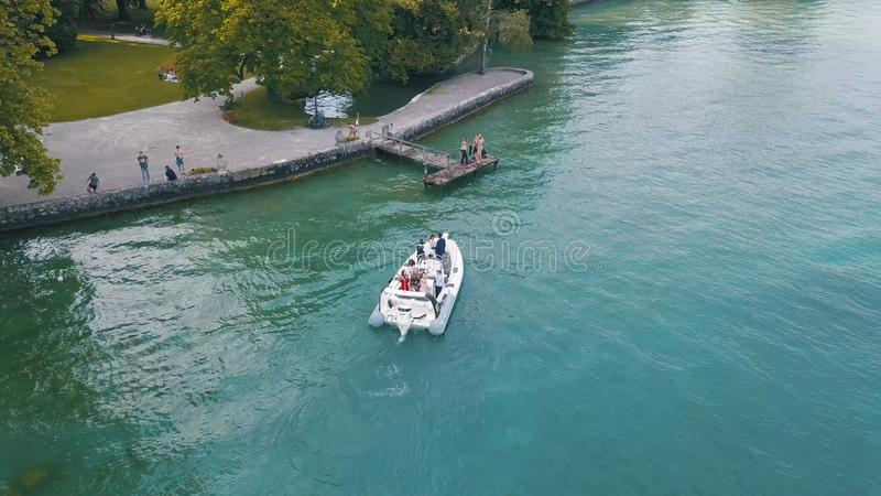 Aerial view of people floating on small white motorboat near the green park. Action. Summer resort royalty free stock image