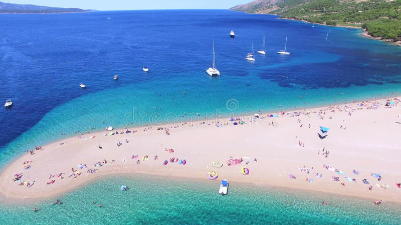 Aerial view of people sunbathing on a sandy beach on the island of Brac, Croatia. Aerial view of people swimming and sunbathing on a sandy beach on the island of stock video