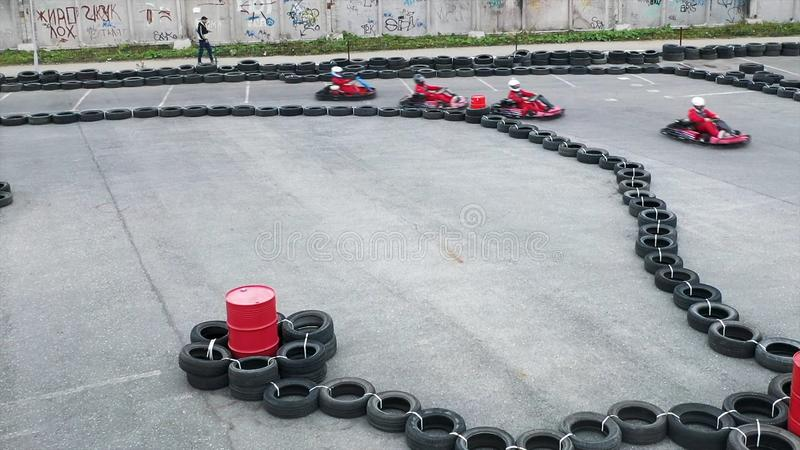 Aerial view of a person driving red small go kart in protective uniform and a helmet on track side made of black tires stock photography