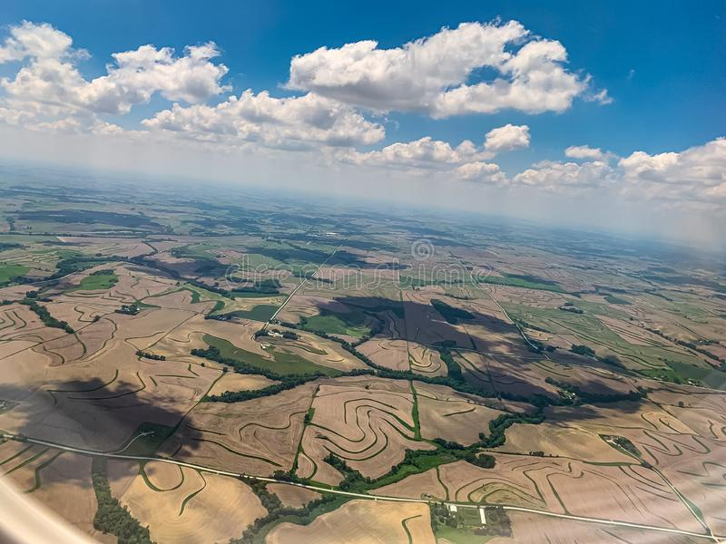 Aerial view farmlands with blue sky in the midwest. Aerial view of picturesque farmlands with blue sky in the midwest.  Shadows of clouds on the ground stock image