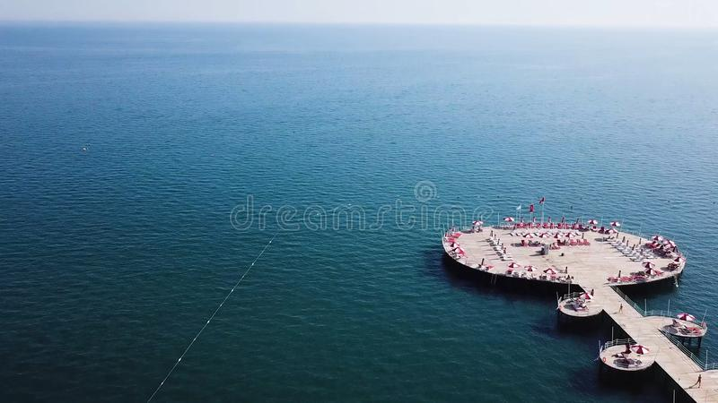 Aerial view on pier of luxury hotel, blue sea background. Video. Aerial top view water villa at Maldives island. Beautiful tropical Maldives resort hotel. Top royalty free stock images