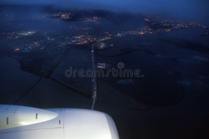 Aerial view Plane jet, salt evaporation ponds, bridge, and cities surrounding San Francisco Bay at dawn royalty free stock image