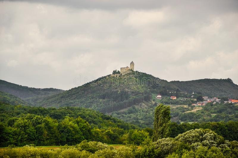 Aerial view of Podhradie Castle and village in Slovakia. Castle on hill with tower surrounded by village and trees with clouds on. The sky royalty free stock photo