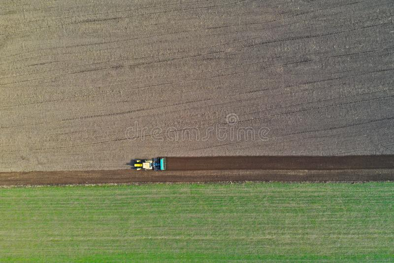 Aerial view on polish rural area with old tractor while plowing the soil on wheat field before sowing the seeds stock photography