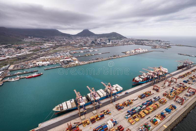 Aerial view of the port with moored container vessels being loaded in the Ben Schoeman Dock showing the city and Table Mountain, C stock image