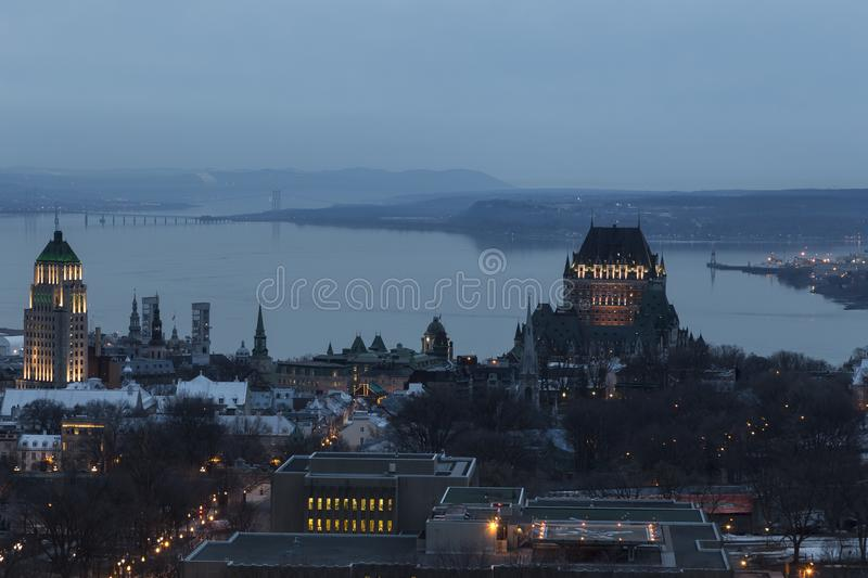 Aerial view of Quebec City`s old town rooftops and buildings at dusk. With the Island of Orleans bridge over the St. Lawrence river and the Laurentian royalty free stock photos