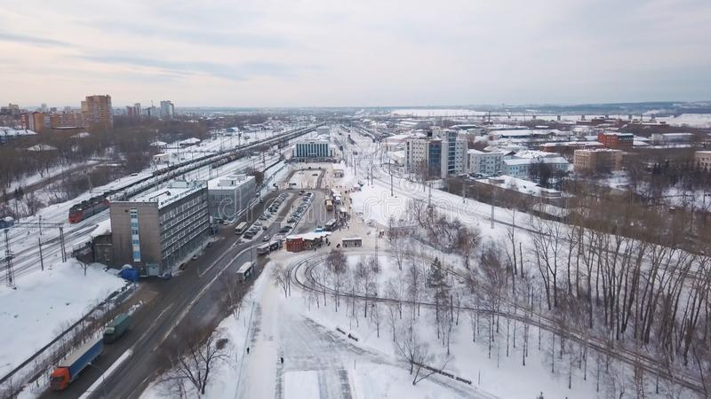 Aerial view of railway station, trains, cars and buildings covered with snow against evening grey sky in winter. Clip royalty free stock photography
