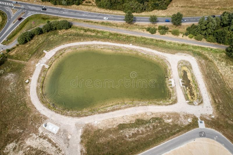 Aerial view of a rain retention basin at the edge of a new development, taken oblique. Aerial view of a rain retention basin at the edge of a new development stock photo