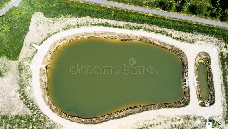 Aerial view of a rain retention basin at the edge of a new development, taken vertically. Germany royalty free stock image