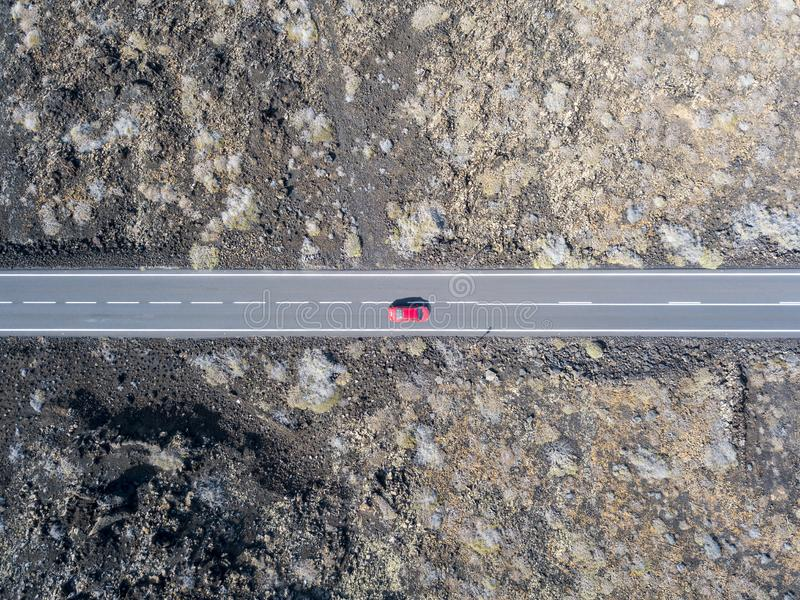 Aerial view of a red car on a road that runs through lava fields of Lanzarote, Canary Islands, Spain. Aerial view of a red car on a road that runs through lava stock photo