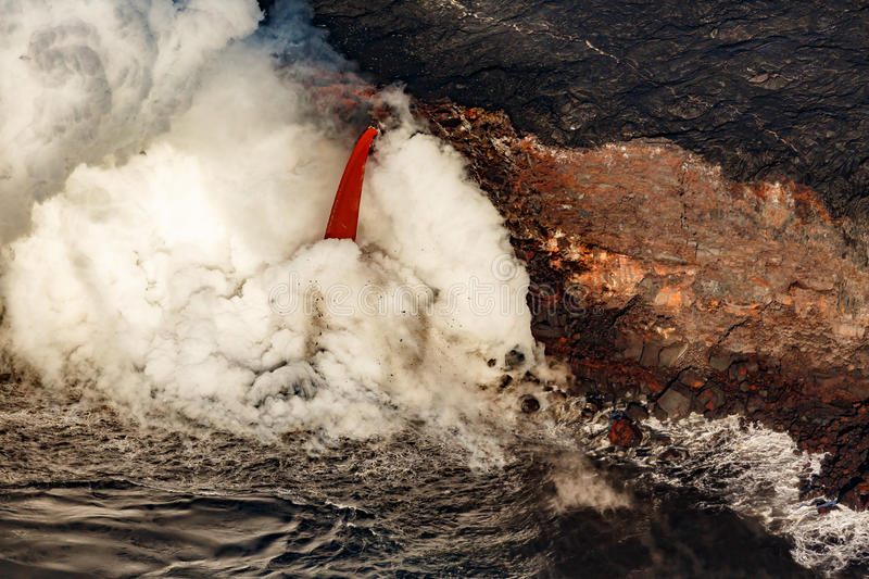 Aerial View of red fire hose shaped lava flow into the ocean on the Hawaiian coast royalty free stock photography